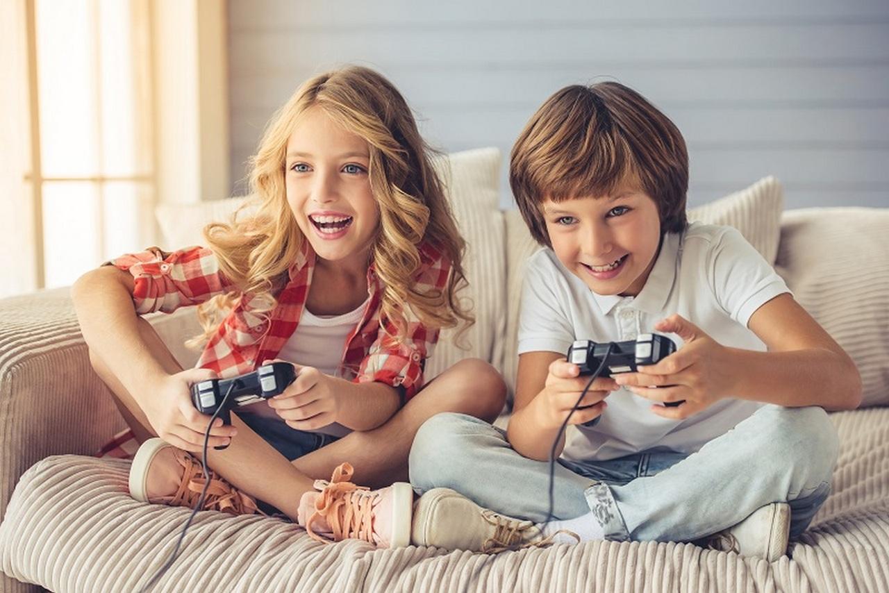 Dziewczynka i chłopiec grający na konsoli